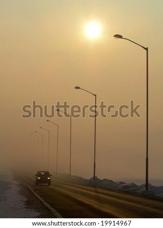 Street lights disappearing in the mist. - stock photo