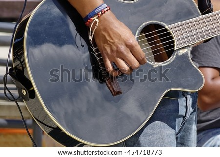 Street Musical Band Play Latin Music. Close-up Of Guitarist Male Hand And Fingers  Who Touches String On The Black Acoustic Guitar - stock photo