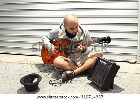 Street musician playing his guitar.  - stock photo