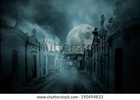 Street of an old european cemetery  in a full moon foggy night - stock photo