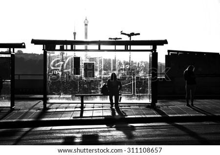 Street photography of someone waiting at a bus stop in black and white. - stock photo