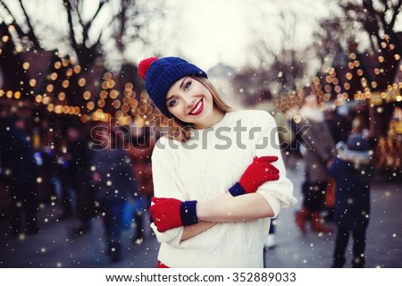 Street portrait of smiling beautiful young woman on the festive Christmas fair. Lady wearing classic stylish winter knitted clothes. Model looking at camera. Magic snowfall effect. Close up - stock photo