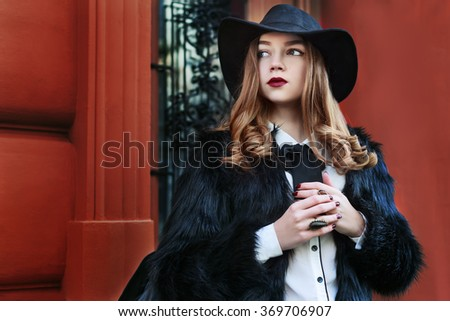 Street portrait of young beautiful lady wearing stylish black fur coat and wide-brimmed hat. Model looking aside. Female fashion  concept. Close up. Colorful background - stock photo