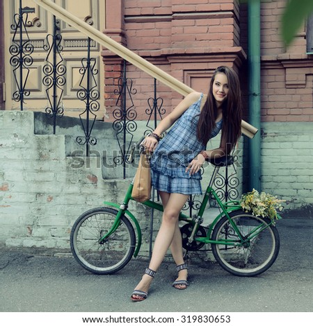 Street portrait of young beautiful woman with bicycle, image toned. - stock photo
