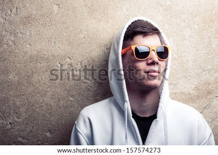 Street portrait of young boy in white sweatshirt with orange modern eyeglasses and hood near old wall, street atmosphere, landscape, young generation, street life - stock photo