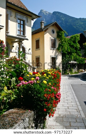 street scene of a french town in the le grand massif, samoens in summer with flowers and mountains in the background - stock photo