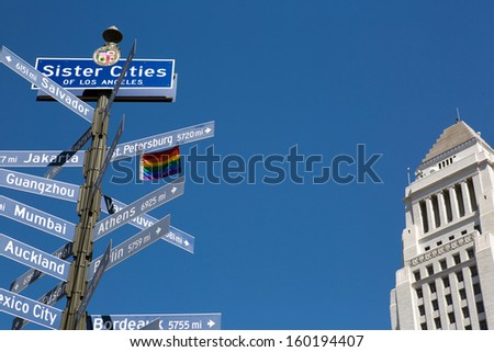 Street sign with the sister cities of Los Angeles and City Hall building - stock photo