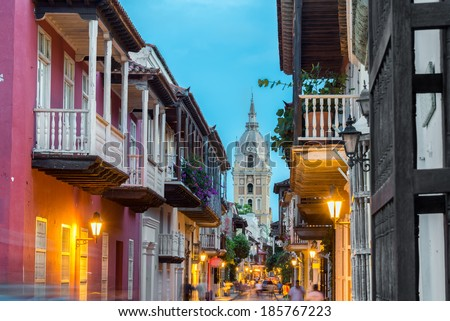 Street view of Cartagena, Colombia after sunset with cathedral visible in the background - stock photo