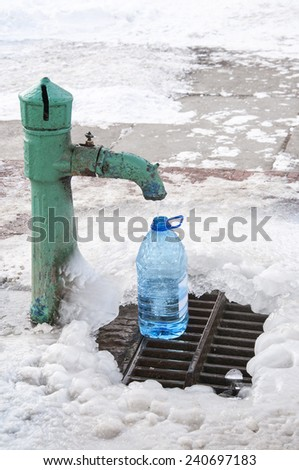 Street water tap pouring water into plastic container, winter time - stock photo