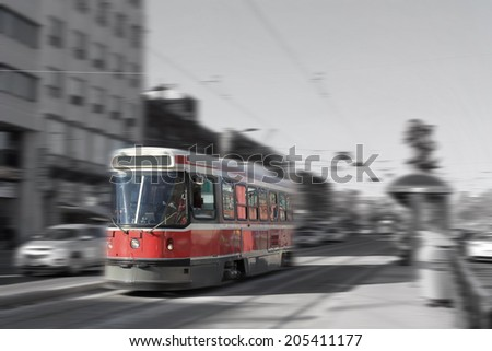 Streetcar transportation in downtown Toronto, Canada with motion blur in black and white and color - stock photo