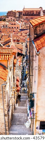Streets of old city Dubrovnik, Croatia during the day. Famous red roofs, cafes, souvenir shops and bars - stock photo