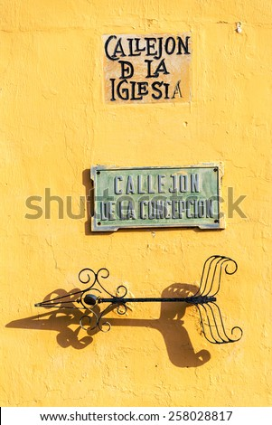 Streets signs on a yellow wall in the historic center of Mompox, Colombia - stock photo