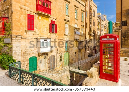 Streetview of Valletta with traditional red balconies, old red phone booth and blue sky - Malta - stock photo