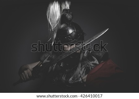 Strengh warrior helmet, armor and red cape on a battlefield, conflict and struggle in the Roman Empire - stock photo
