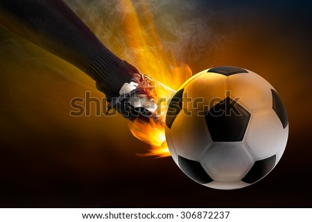 Strength of athlete to kicking the soccer ball with power fire blaze in dark background - stock photo