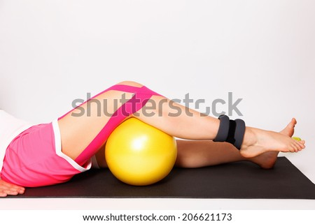 Strengthening exercise for injured leg with kinesiology tape and - stock photo