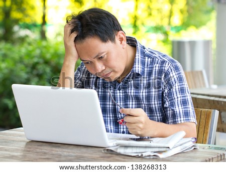 Stress Asian man looking at laptop. - stock photo