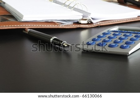 stress at work in the office concept with calculator and paperwork - stock photo