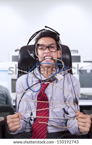 Stress businessman tied in rope and cables at office - stock photo