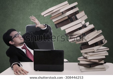 Stress businessman with falling books and blank blackboard - stock photo