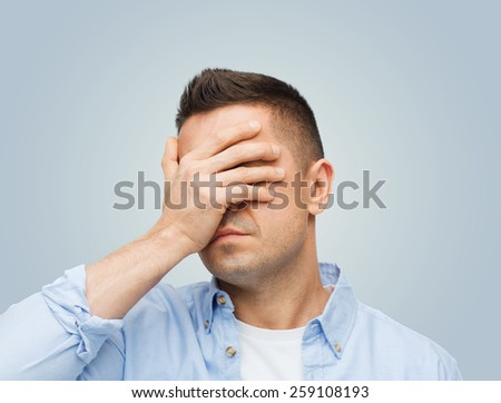 stress, headache, health care and people concept - unhappy man covering his eyes by hand over gray background - stock photo