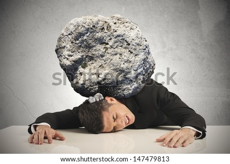 Stress of a businessman with a big rock - stock photo