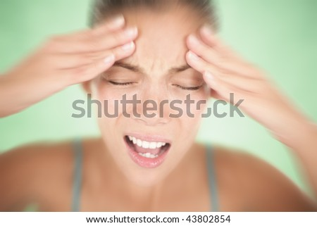 Stress woman having a migraine / headache holding her head in pain and stress. Shallow depth of field on green background. - stock photo