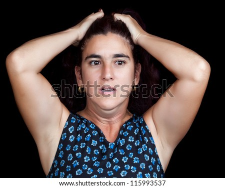 Stressed and depressed woman with her hands on her head and a very sad face isolated on black with space for text - stock photo
