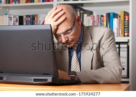 Stressed and frustrated elderly man in front of his laptop - stock photo