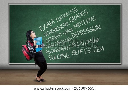 Stressed asian student having many problems in a classroom - stock photo