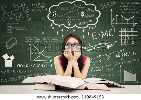 Stressed Asian student in a classroom. Shot against blackboard with formula from many different subjects - stock photo