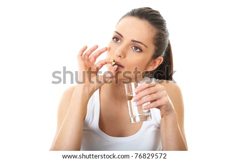 stressed attractive young brunette take some pills, holds glass of water, isolated on white - stock photo