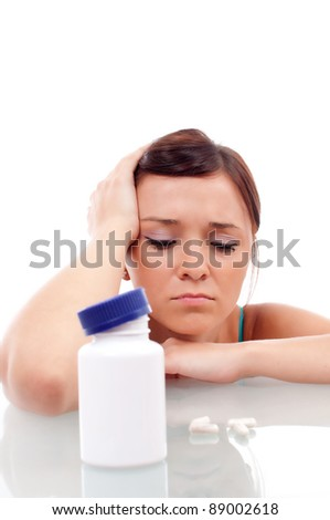 stressed attractive young brunette with some pills, isolated on white - stock photo