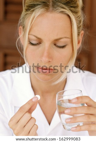 stressed attractive young holds some pills - stock photo