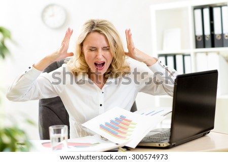 Stressed business woman at laptop in office - stock photo