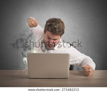 Stressed businessman breaks the computer with punch - stock photo