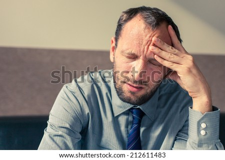 Stressed businessman getting a headache at home in the living room - stock photo