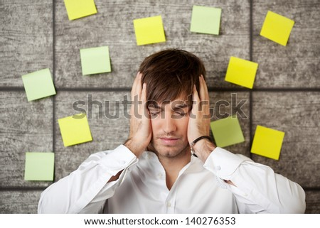 Stressed businessman holding his head between hands on wooden background - stock photo