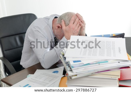 Stressed businessman holding his head in his hands - stock photo