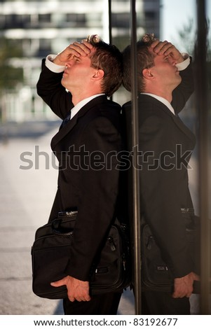 Stressed businessman leaning on an office building - stock photo