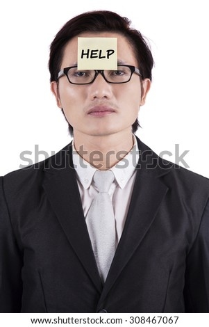 Stressed businessman needs a help and attach a help text on his forehead - stock photo