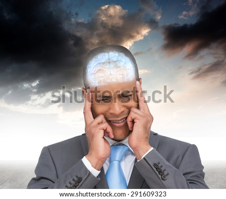 Stressed businessman putting his fingers on his temples against blue sky - stock photo