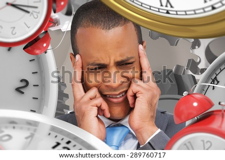 Stressed businessman putting his fingers on his temples against grey background with vignette - stock photo