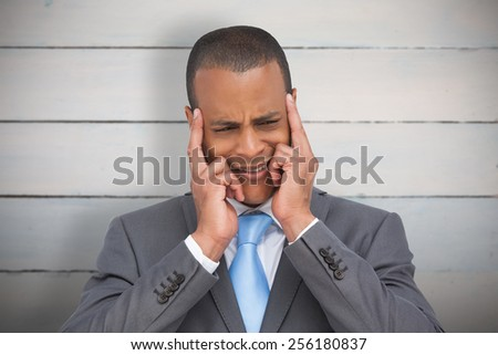 Stressed businessman putting his fingers on his temples against painted blue wooden planks - stock photo