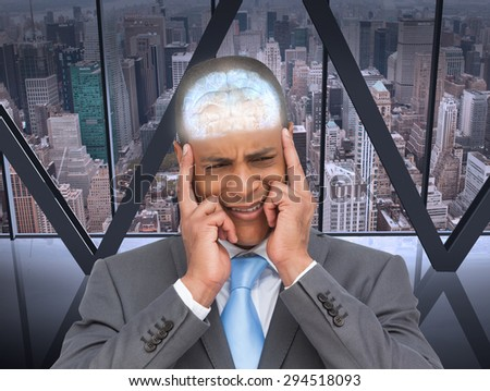 Stressed businessman putting his fingers on his temples against room with large window looking on city - stock photo