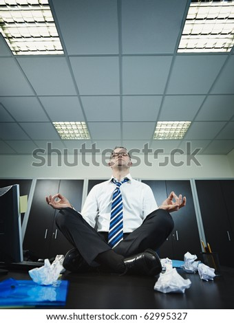 stressed businessman sitting on desk in lotus position. Vertical shape, full length, Copy space - stock photo