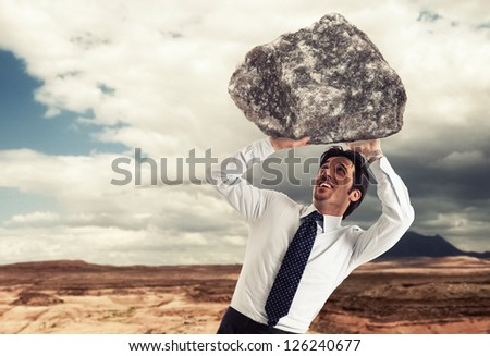 Stressed businessman trying to lift a rock - stock photo