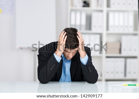 Stressed businessman with head in hands at desk in office - stock photo