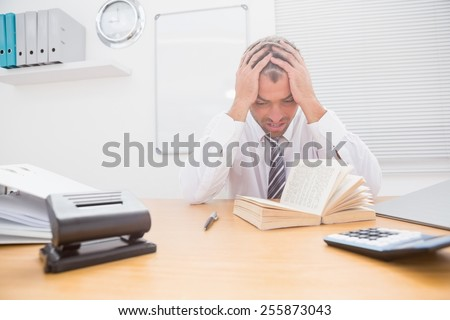 Stressed businessman with head in hands in his office - stock photo