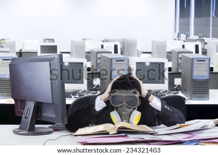 Stressed businessman with mask in an office - stock photo